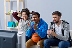 Amis observant le sport à la TV Photos stock