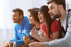 Amis observant le sport à la TV Images libres de droits