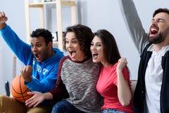Amis observant le sport à la TV Photographie stock libre de droits
