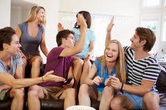 Amis observant le sport célébrer le but Images stock