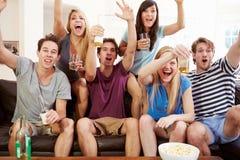Amis observant le sport célébrer le but Image libre de droits