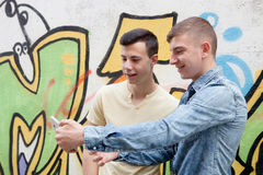 Amis observant le téléphone dans la rue Images libres de droits
