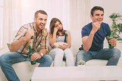 Amis observant A TV dans la maison Images stock
