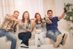 Amis observant A TV dans la maison Images libres de droits