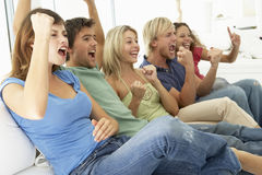 Amis observant un jeu à la télévision Image stock