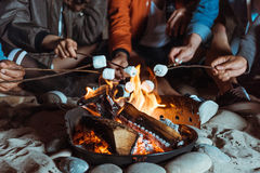 Amis occasionnels rôtissant des guimauves sur le feu Images stock