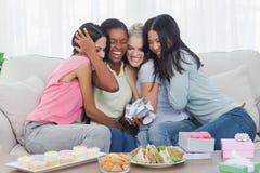 Amis offrant des cadeaux et étreignant la femme pendant la partie Image stock