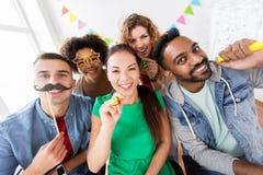 Amis ou équipe heureux ayant l'amusement à la fête au bureau Photos stock