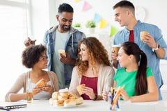 Amis ou équipe heureux mangeant à la fête au bureau Photo libre de droits