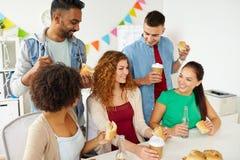 Amis ou équipe heureux mangeant à la fête au bureau Photographie stock libre de droits
