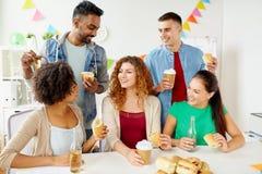 Amis ou équipe heureux mangeant à la fête au bureau Photo stock
