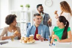 Amis ou équipe heureux mangeant à la fête au bureau Image stock