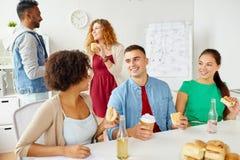Amis ou équipe heureux mangeant au bureau Image stock