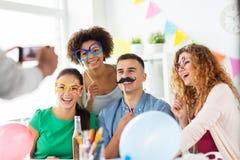 Amis ou équipe photographiant à la fête au bureau Photographie stock