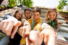 Amis ou étudiants adolescents dirigeant le doigt à vous Image stock