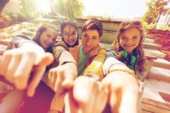 Amis ou étudiants adolescents dirigeant le doigt à vous Photo stock
