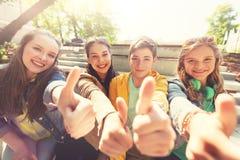 Amis ou étudiants adolescents montrant des pouces  Photos libres de droits