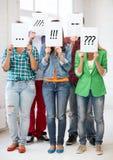 Amis ou étudiants couvrant des visages de papiers Images stock