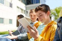 Amis ou étudiants heureux avec le PC de comprimé dehors Image stock