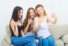 Amis ou adolescentes heureux avec le smartphone prenant le selfie Photos libres de droits