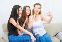 Amis ou adolescentes heureux avec le smartphone prenant le selfie Images libres de droits