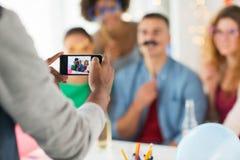 Amis ou collègues photographiant à la fête au bureau Images stock