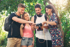 Amis ou couples ayant l'amusement avec l'appareil-photo de photo dans le parc Photographie stock libre de droits