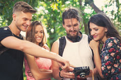 Amis ou couples ayant l'amusement avec l'appareil-photo de photo dans le parc Images libres de droits