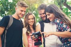 Amis ou couples ayant l'amusement avec l'appareil-photo de photo dans le parc Photographie stock