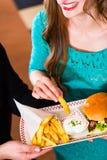 Amis ou couples mangeant des aliments de préparation rapide avec l'hamburger et les fritures Photo libre de droits