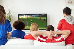 Amis ou fans de foot observant le jeu à la TV à la maison Photographie stock libre de droits