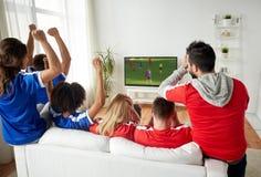Amis ou fans de foot observant le jeu à la TV à la maison Image libre de droits