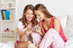 Amis ou filles d'ado avec le smartphone à la maison Image libre de droits