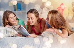 Amis ou filles d'ado lisant le magazine à la maison Image libre de droits