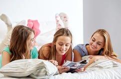 Amis ou filles d'ado lisant le magazine à la maison Image stock