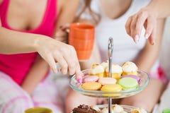 Amis ou filles d'ado mangeant des bonbons à la maison Photographie stock libre de droits