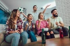 Amis ou passionés du football heureux observant le football à la TV Photo stock