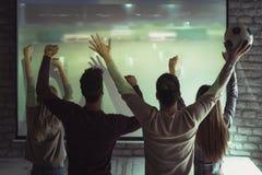 Amis ou passionés du football heureux observant le football à la TV Photos libres de droits