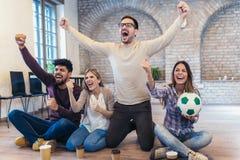 Amis ou passionés du football heureux observant le football à la TV Photos stock