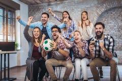 Amis ou passionés du football heureux observant le football à la TV et célébrant la victoire Photo stock