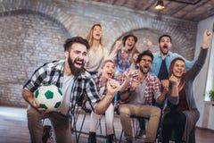 Amis ou passionés du football heureux observant le football à la TV et célébrant la victoire Image libre de droits