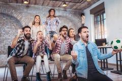 Amis ou passionés du football heureux observant le football à la TV et célébrant la victoire Image stock