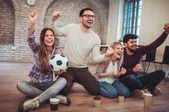 Amis ou passionés du football heureux observant le football à la TV et célébrant la victoire Photographie stock libre de droits