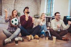 Amis ou passionés du football heureux observant le football à la TV et célébrant la victoire Images libres de droits