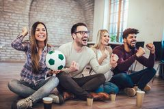 Amis ou passionés du football heureux observant le football à la TV et célébrant la victoire Photographie stock