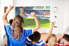 Amis ou passionés du football heureux observant le football Images stock