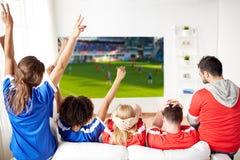 Amis ou passionés du football heureux observant le football Photos stock