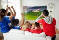 Amis ou passionés du football observant le football Image stock