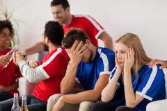 Amis ou passionés du football observant le football à la maison Image stock