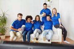 Amis ou passionés du football observant le football à la maison Images stock